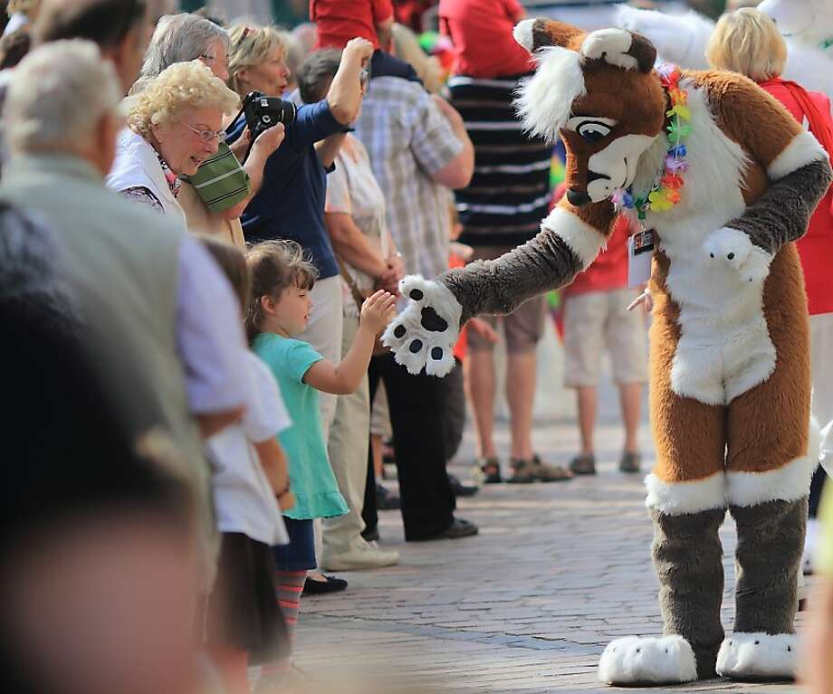 A fox shakes pawswith a little girl at Eurofurence Convention, a meeting of furry fandom in Magdeburg, Germany. Some 1,400 plushy-animal enthusiasts were expected to attend. Photo: Jens Wolf, AFP/Getty Images
