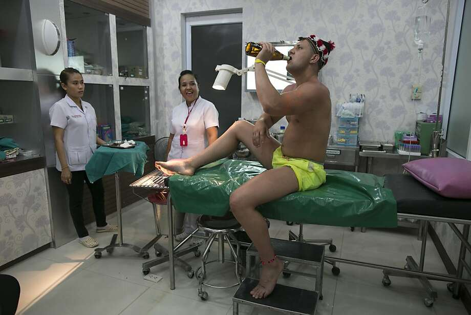 Anesthesia:Scot Jamie Harris downs a beer at clinic in Koh Phangan, Thailand, before getting treated for an foot injury he suffered at the full-moon party. Photo: Paula Bronstein, Getty Images