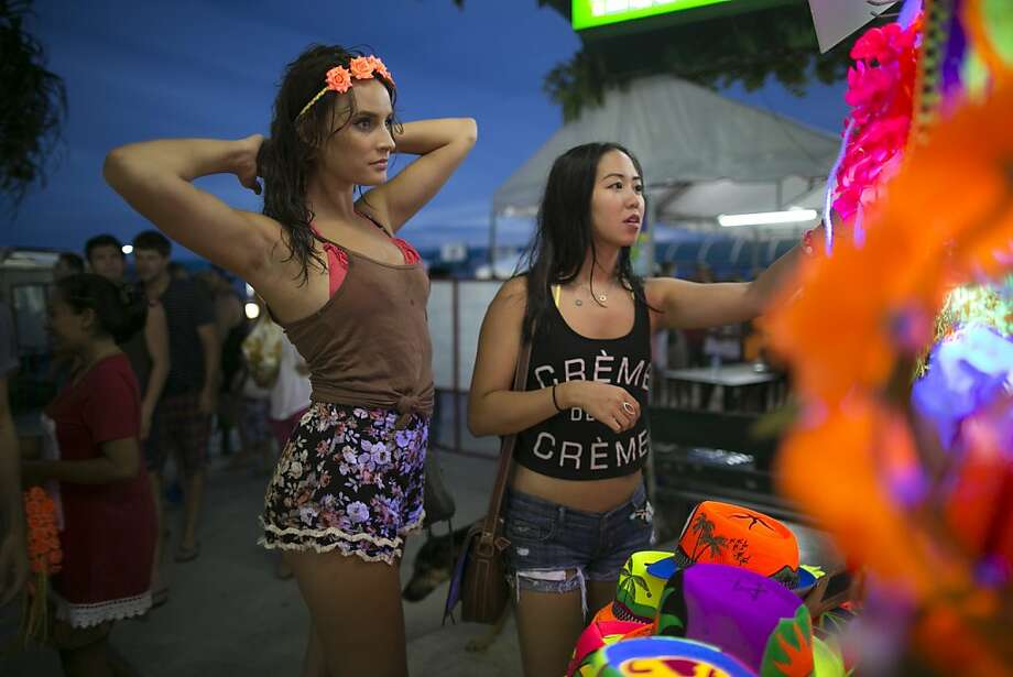 Preparing for an all-nighter: Tourists shop for headbands for the full-moon party on the island of Koh Phangan, Thailand. Every year, thousands of young travelers pack Haad Rin beach to enjoy music, cheap liquor and drugs during a bash that doesn't end until sunrise.  Photo: Paula Bronstein, Getty Images