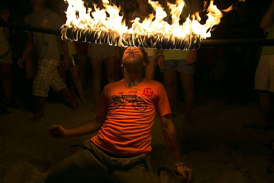 Light my fire: A tourist tries to light a cigarette on a flaming bar while limboing underneath it during the all-night full-moon beach party in Koh Phangan, Thailand. Photo: Paula Bronstein, Getty Images