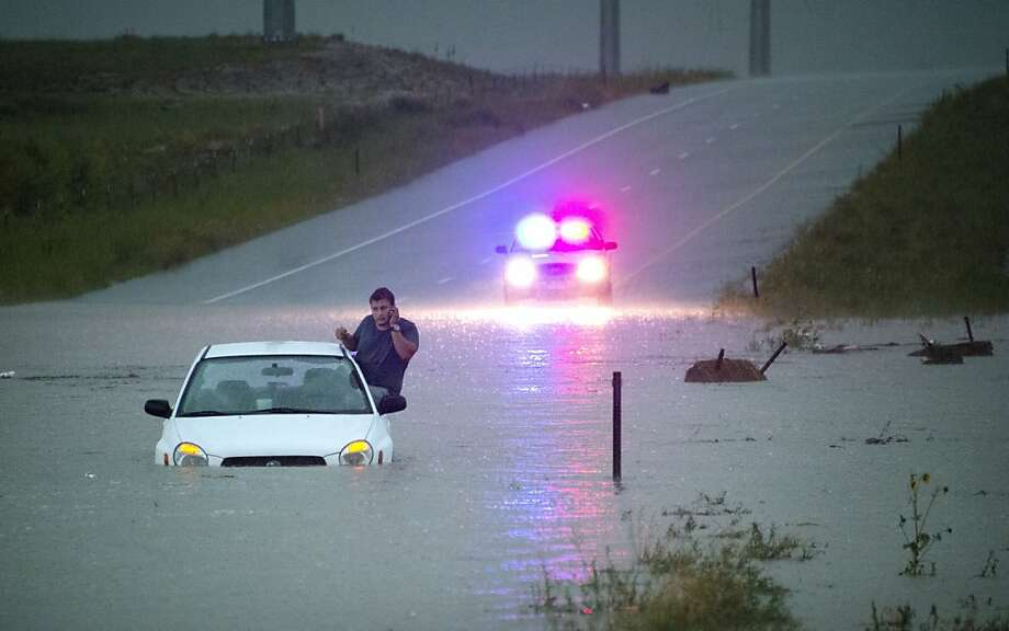 But it didn't seem that deep ... A stranded motorist makes a call while waiting for help in Colorado Springs, Colo., after a slow-moving storm dropped about three inches of rain. The water eventually subsided, and the man ended up walking away from the car. Photo: Mark Reis, Associated Press