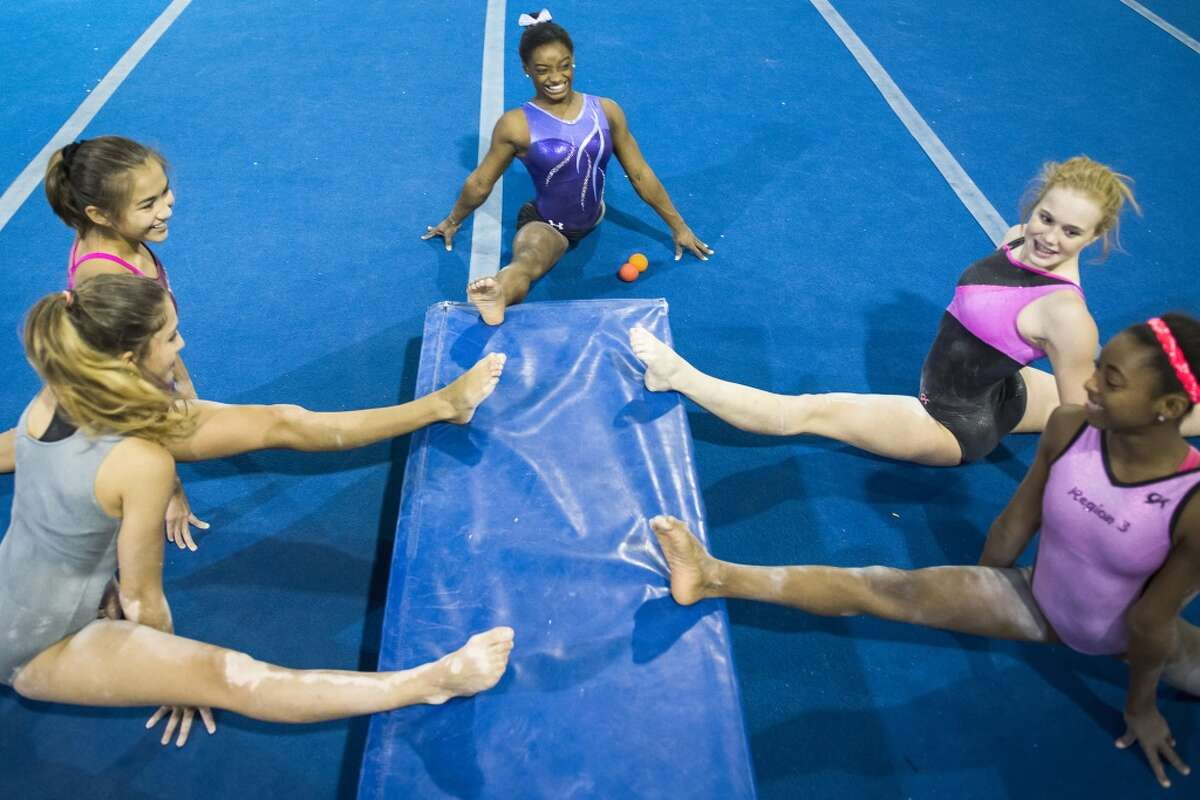 Simone Biles, top, stretches with her teammates after training.