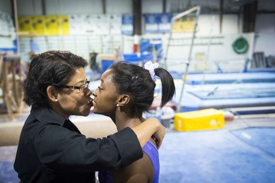 Simone Biles gets a kiss from her mother Nellie Biles as she trains at Bannon's Gymnastix on Thursday, Aug. 22, 2013. Photo: Smiley N. Pool, Houston Chronicle