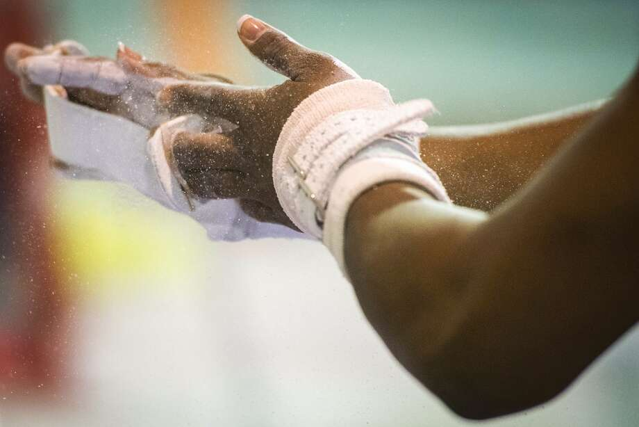Simone Biles chalks her hands before training on the uneven bars at BannonÕs Gymnastix. Photo: Smiley N. Pool, Houston Chronicle