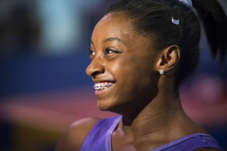 Simone Biles smiles while doing a television interview. Photo: Smiley N. Pool, Houston Chronicle
