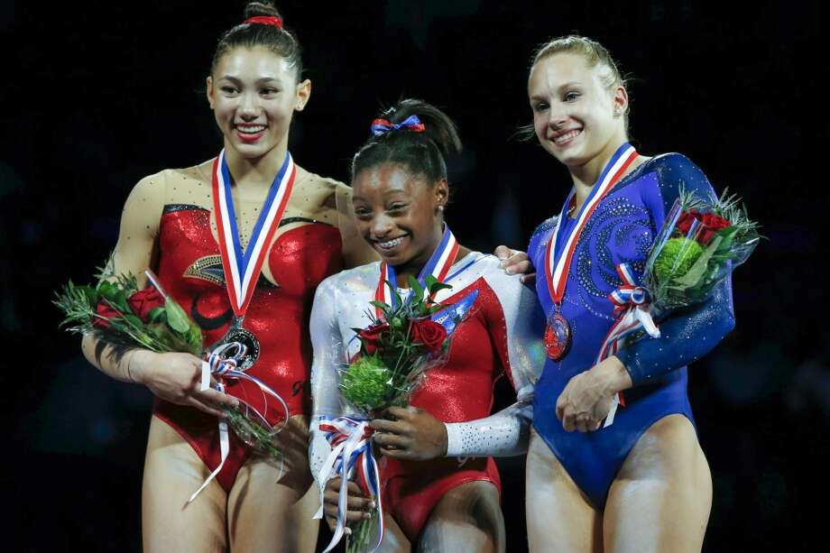 Simone Biles, center, reacts during the medals ceremony at the U.S. women's national gymnastics championships in Hartford, Conn., Saturday, Aug. 17, 2013. Biles won the gymnastics title, edging Kyla Ross, left, who came in second. Third-place finisher Brenna Dowell, right, smiles. Photo: Elise Amendola, Associated Press