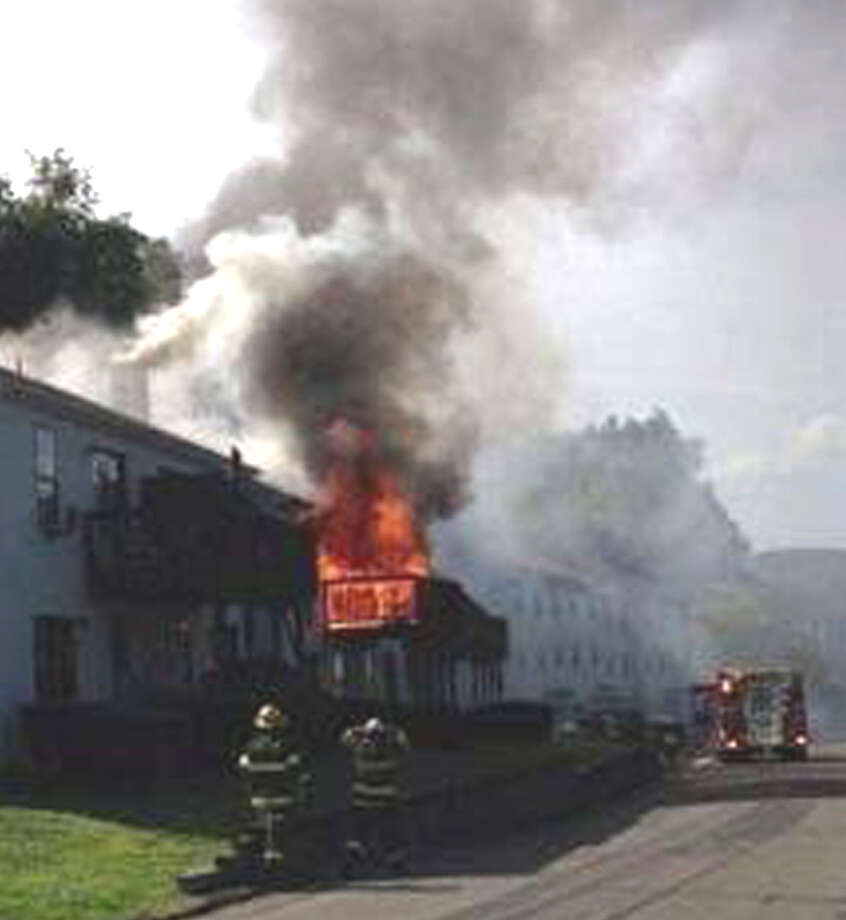 Firefighters battle a blaze at 105 Aspetuck Village Friday, Aug. 23, 2013 in New Milford. Photo: Contributed Photo