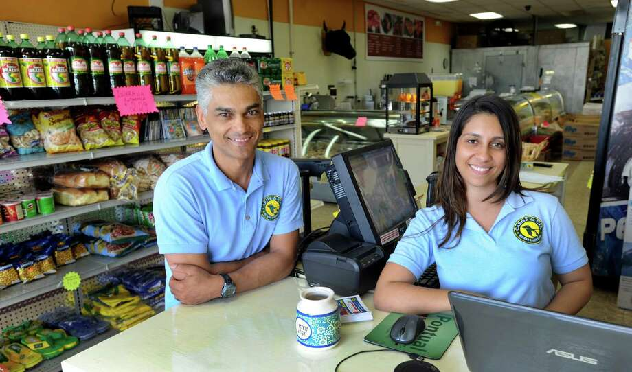 Breno DaMata, left, owner of Carne & Cia, and his daughter Ana, work together at his store on White Street in Danbury, Conn., Friday, Aug. 23, 2013. Photo: Carol Kaliff / The News-Times