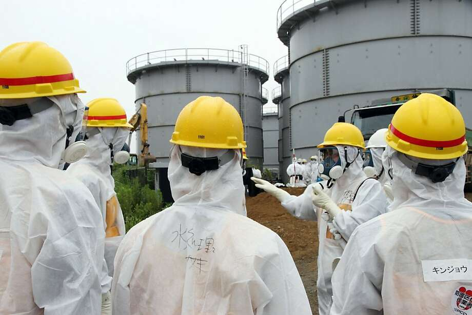 Japan's nuclear watchdog members, including Nuclear Regulation Authority members in radiation protection suits, inspect contaminated water tanks at the Tokyo Electric Power Co (TEPCO) Fukushima Dai-ichi nuclear power plant in the town of Okuma, Fukushima prefecture on August 23, 2013.  Japan's nuclear watchdog dispatched an inspection team to the crippled Fukushima plant after workers found a huge toxic water leak and unexplained radiation hotspots.  Earlier this week around 300 tonnes of radioactive liquid is believed to have escaped from one of the hundreds of tanks that hold polluted water, some of which was used to cool the broken reactors, in an episode dubbed the most serious in nearly two years. Photo: Japan Pool, AFP/Getty Images