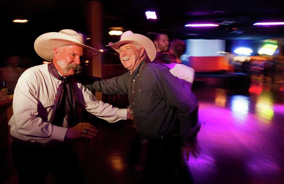 Jim Gerhold and Jim Moore dance at the Neon Boots Dancehall and Saloon, a country-style gay, lesbian and transgender bar located in the former home of the Esquire Ballroom. Photo: Johnny Hanson, Staff / © 2013  Houston Chronicle