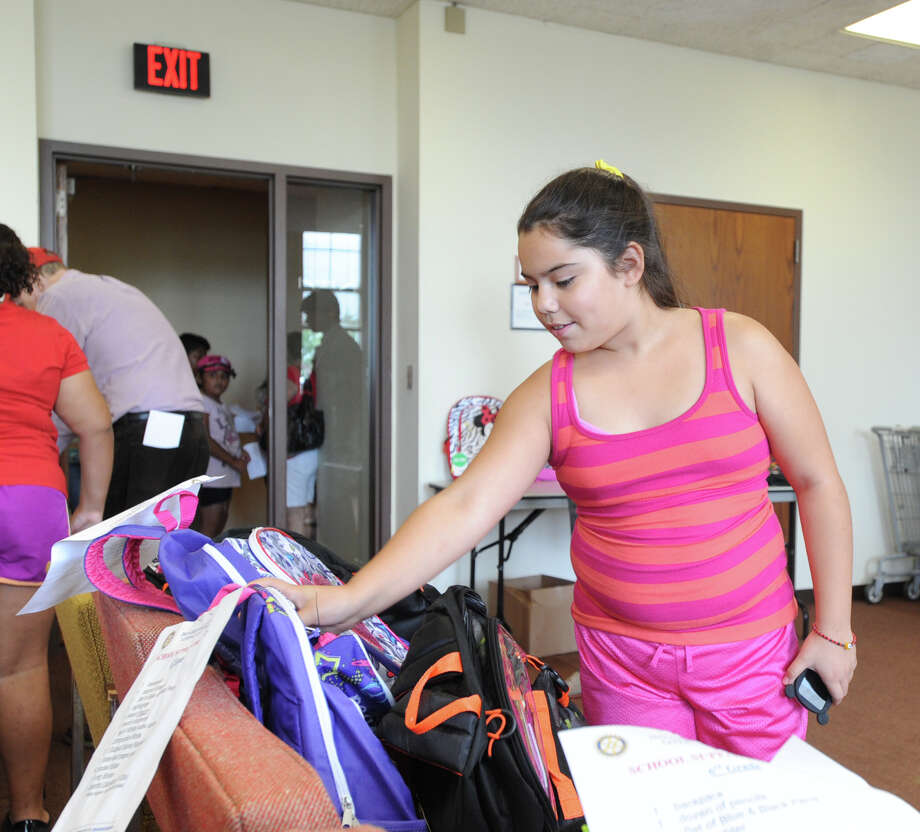 Zitlalic Tejeda, 11, of Greenwich, selects a backpack during the Department of Social Services distribution of backpacks and school supplies to students at Greenwich Town Hall, Friday afternoon, August 23, 2013. Tejeda will be attending Western Middle School as a sixth grade student. The Rotary Club of Greenwich funded the purchase of the backpacks and school supplies. Photo: Bob Luckey / Greenwich Time