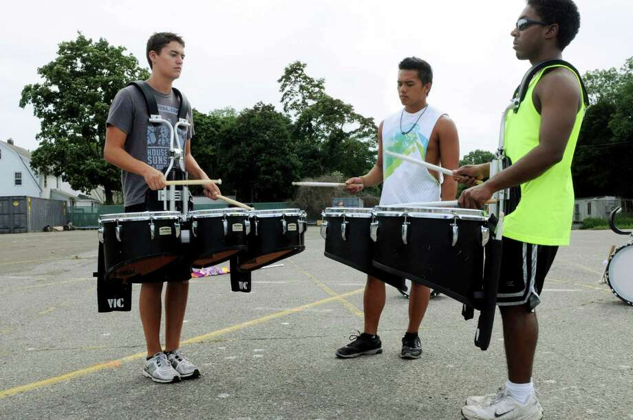Assistant band director Omi Batan ( center) helps Marc Marenco and Anthony Flores with thier tenor drums at Stamford ( Conn. ) High School marching band camp in the parking lot behind the school on Friday August 23, 2013. Photo: Dru Nadler / Stamford Advocate Freelance