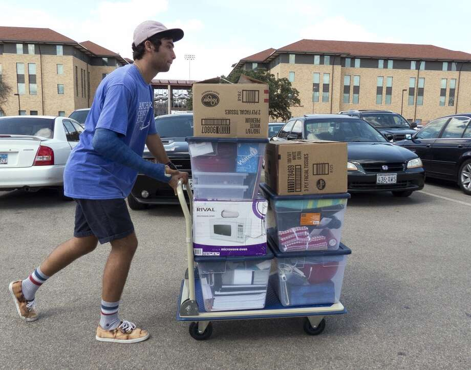 Volunteer Colton Bolin helps students move their belongings into the new San Saba residence hall at The University of Texas at San Antonio on Friday, Aug. 23, 2013. Photo: Billy Calzada / San Antonio Express-News