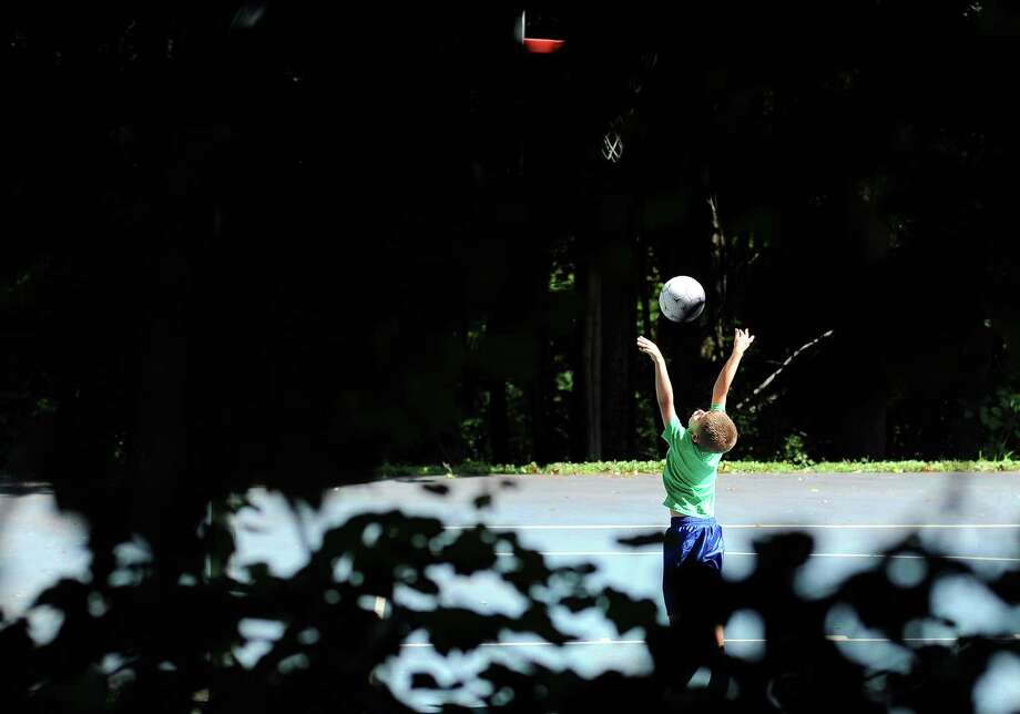 Tyler Yacawych, 7, of Seymour, shoots hoops at Gary Park in Seymour, Conn. Friday, Aug. 23, 2013. Photo: Autumn Driscoll / Connecticut Post
