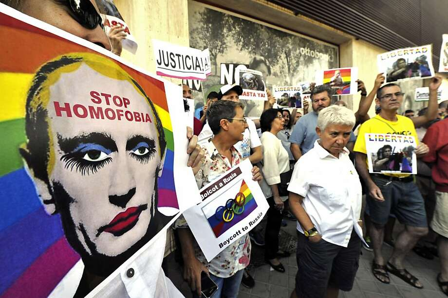 Demonstrators at the Russian Embassy in Madrid hold posters depicting Russian President Vladimir Putin with makeup. Photo: Gerard Julien, AFP/Getty Images