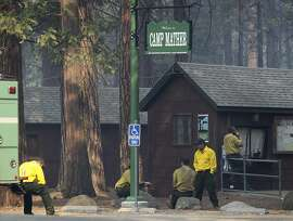 Firefighters take a break after protecting Camp Mather from the Rim Fire near Yosemite National Park on Friday, Aug. 23, 2013. The wildfire, one of the largest in the nation, has scorched over 150 square miles of terrain.