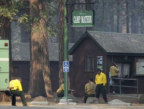 Firefighters take a break after protecting Camp Mather from the Rim Fire near Yosemite National Park on Friday, Aug. 23, 2013. The wildfire, one of the largest in the nation, has scorched over 150 square miles of terrain. Photo: Paul Chinn, The Chronicle