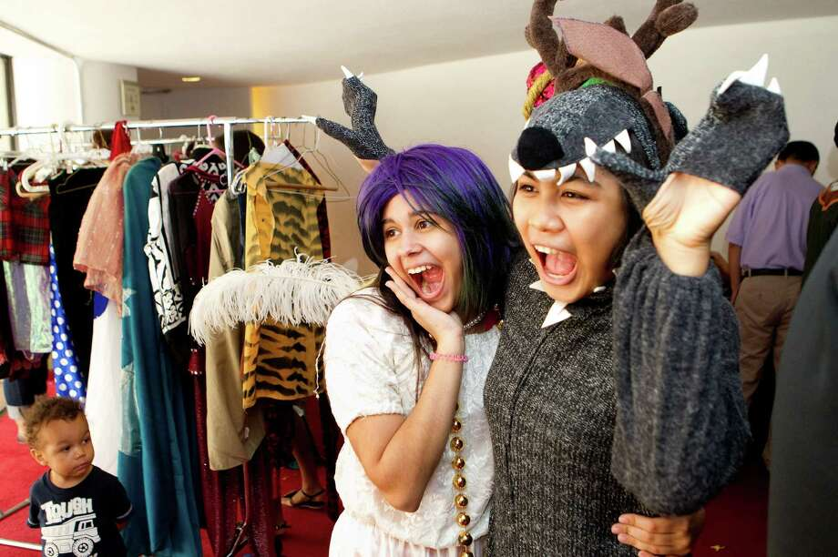 Andrea Bonnin, 16, left, and Fiang Boonyarat, 17, right, take a photo as they try on costumes during the 19th annual Theater District Open House, at Alley Theatre Sunday, Aug. 26, 2012, in Houston. The open house had different activities including backstage tours, live performances by professional and community entertainers and allowed attendees to try on costumes. It also allowed attendees to learn more about the arts and Houston's nine major performing arts organizations: Alley Theatre; Da Camera of Houston; Gexa Energy Broadway at the Hobby Center; Houston Ballet; Houston Grand Opera; Houston Symphony; Society for the Performing Arts; Theatre Under The Stars and Uniquely Houston. (Cody Duty / Houston Chronicle) Photo: Cody Duty, Staff / © 2011 Houston Chronicle