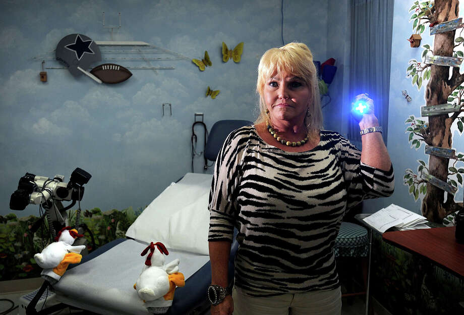Brenda Garrison a Beaumont based sexual assault nurse examiner stands in an examining room while holding a black light used in a rape investigation. As a reaction to a new law requiring some hospitals to employ a forensic nurse, Garrison believes a regional approach would be more effective and less of a cost burden on smaller hospitals. Photo taken Friday, August 23, 2013 Guiseppe Barranco/The Enterprise Photo: Guiseppe Barranco, STAFF PHOTOGRAPHER / The Beaumont Enterprise