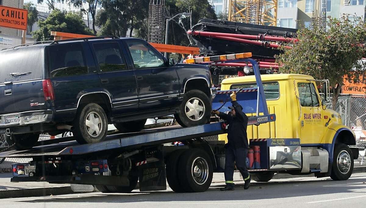 A tow truck driver hooks a car onto a tow truck on Franklin St. on Tuesday, Sept. 20. Board of Supervisors President David Chiu is proposing a new program that will alert drivers to upcoming tows via text, emails, or robocalls.