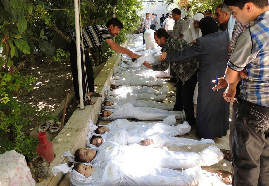 In this photo provided by the Local Committee of Arbeen, which has been authenticated based on its contents and other Associated Press reporting, Syrian citizens try to identify dead bodies after an alleged poisonous gas attack, according to activists in Arbeen town on Wednesday. Photo: Uncredited, HOEP / Local Committee of Arbeen