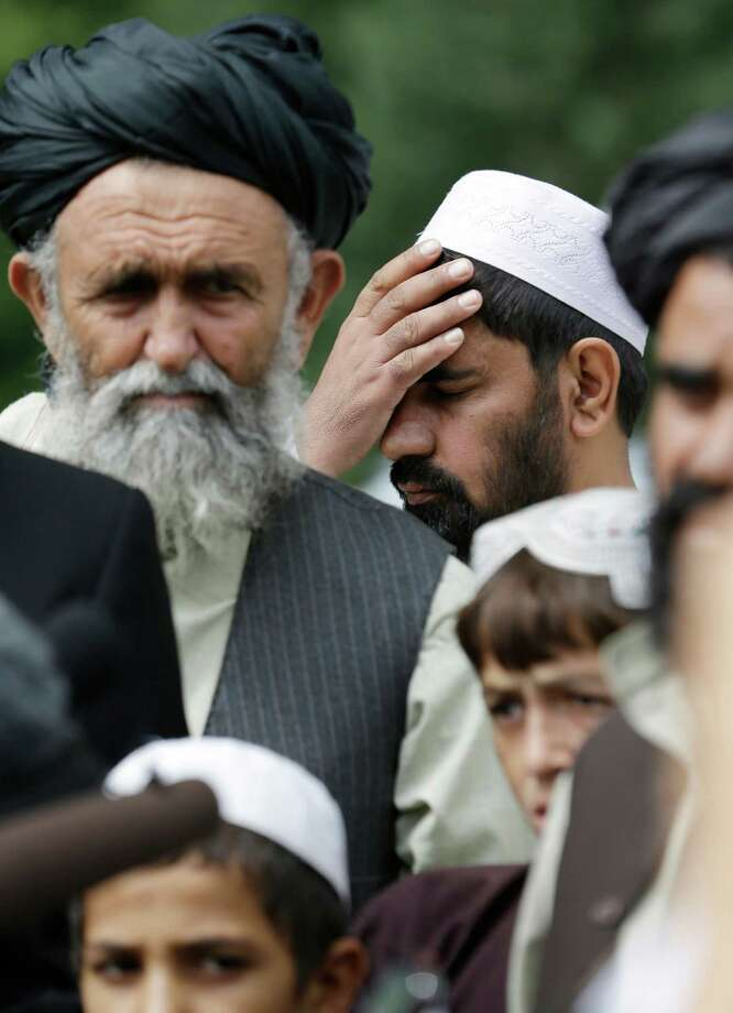 An Afghan villager holds his head as he and others criticized the life term given Staff Sgt. Robert Bales in the massacre of 16 civilians in 2012.