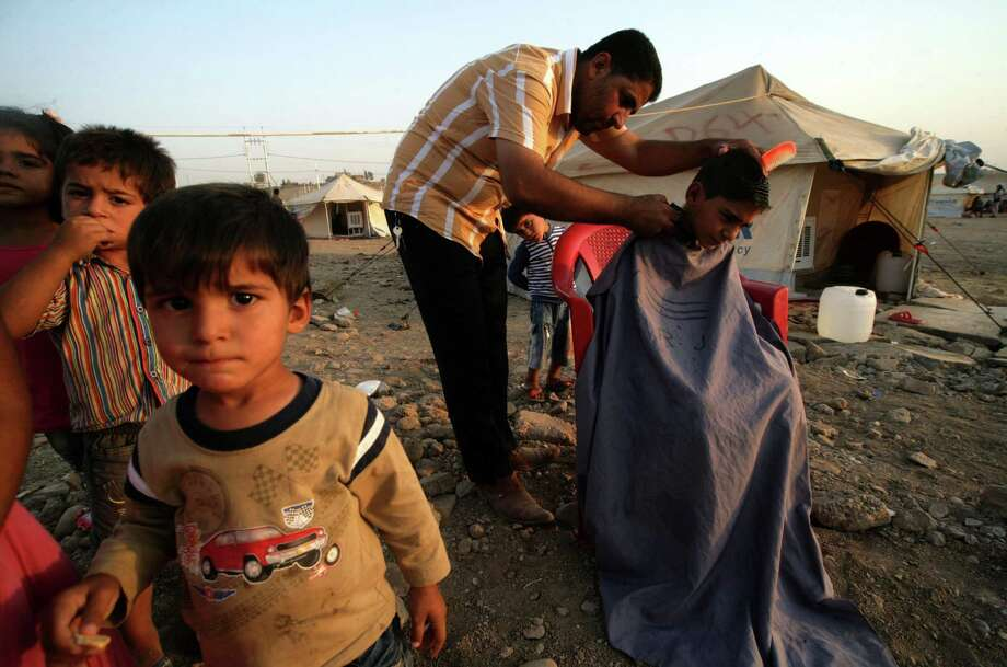 A Syrian-Kurdish man give a boy a haircut at the Quru Gusik refugee camp in northern Iraq. Thousands of Syrian Kurds have poured into the Iraq region. Photo: SAFIN HAMED, Stringer / AFP