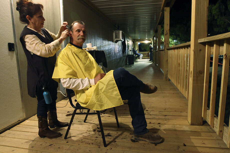 "Alan Roberts, 53, gets a haircut from Josie Wimberley at a ""man camp"" in Carrizo Springs. Transient employees such as oil-field workers are not counted in the U.S. Census, which is used to determine a region's water needs. Photo: Express-News File Photo"