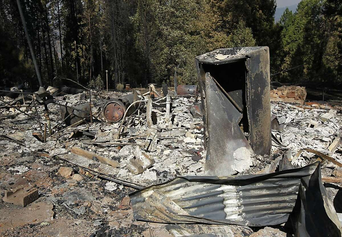 Charred rubble is all that remains of a home on Packard Canyon Road near Highway 120 in Tuolumne County. Thousands have fled homes in the area.
