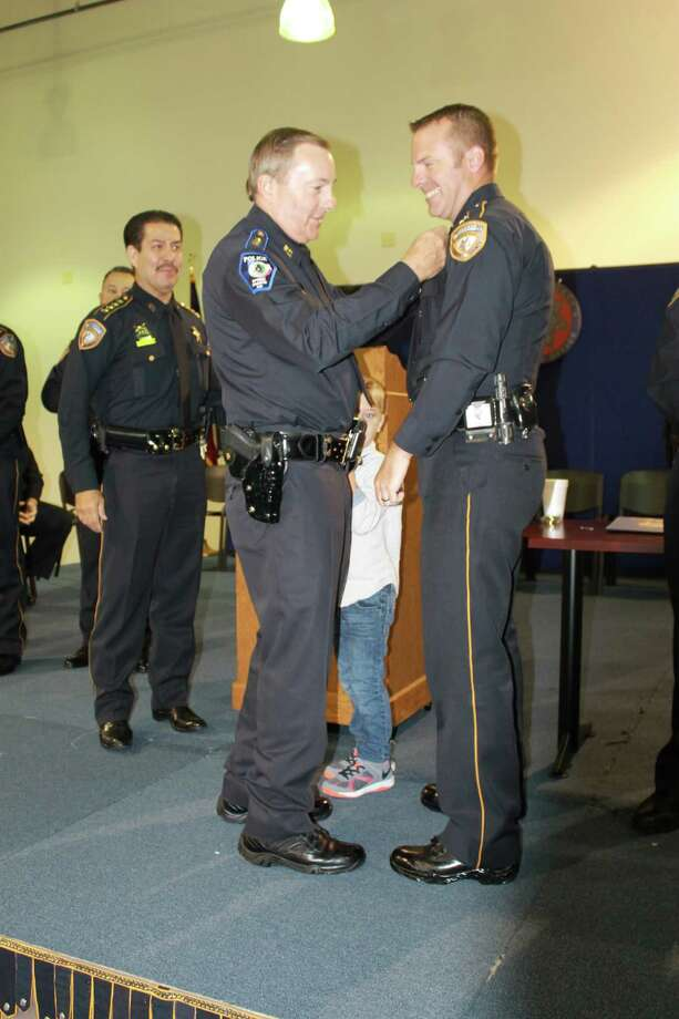 Chief Chuck Brawner of the Harris County Sheriff's Office pins a new sergeant's badge on his son, Brian Brawner, during a promotion ceremony Aug. 16. Photo: Provided By Harris County Sheriff's Office.