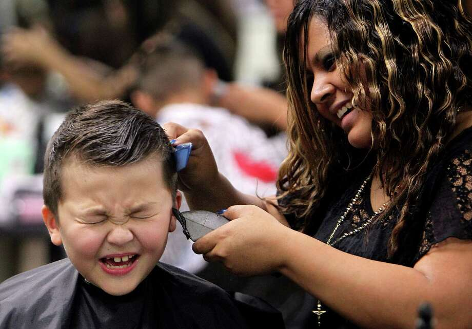 Preston Rose, 9, closes his eyes as stylist Diana Plata uses clippers to trim hair around the ears while giving a free haircut in preparation for the first day of school at SuperCuts Studio on Friday, Aug. 23, 2013, in Houston. Photo: Mayra Beltran, Houston Chronicle / © 2013 Houston Chronicle