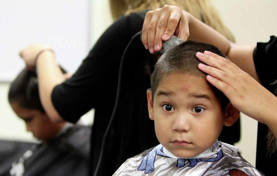Xavier Gone, 5, sits quietly as stylist give him a free haircut in preparation for the first day of school at SuperCuts Studio on Friday, Aug. 23, 2013, in Houston. Photo: Mayra Beltran, Houston Chronicle / © 2013 Houston Chronicle