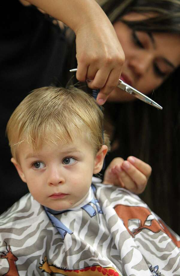 A stylist gives Gideon Crane, 2, a free haircut in preparation for the first day of school at SuperCuts Studio on Friday, Aug. 23, 2013, in Houston. Photo: Mayra Beltran, Houston Chronicle / © 2013 Houston Chronicle