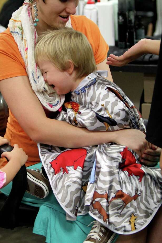 Gideon Crane, 2, cries as his mother and stylist attempt give him a free haircut in preparation for the first day of school at SuperCuts Studio on Friday, Aug. 23, 2013, in Houston. Photo: Mayra Beltran, Houston Chronicle / © 2013 Houston Chronicle