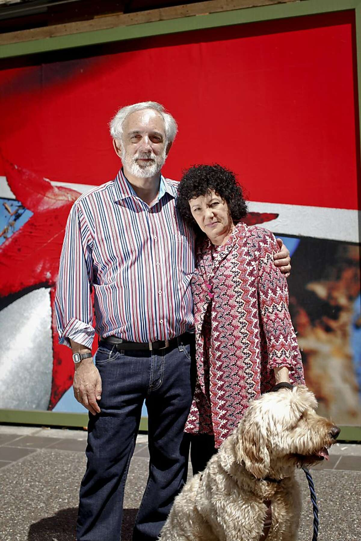Mitch Kapor and Freada Kapor Klein and their dog, Dudley, stand in front of the new home of the Kapor Center for Social Impact that they are renovating in Oakland, Calif., on Wednesday, June 20, 2013.