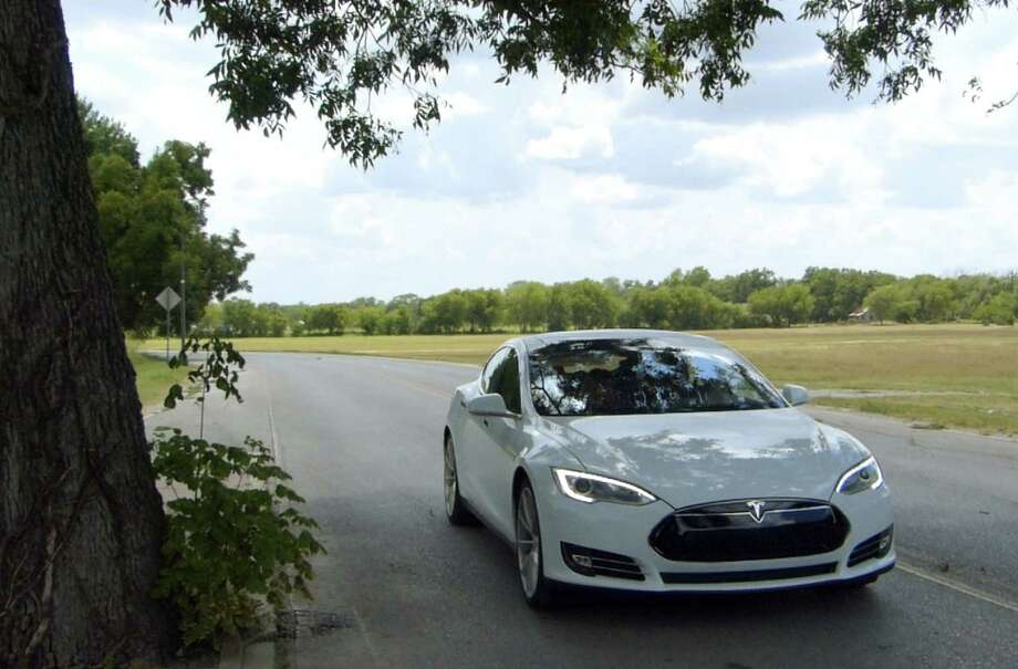 An all-electric Tesla Model S sedan makes its way in San Antonio during a test drive this week. Pre-sales in Hong Kong have surpassed demand in the United Kingdom, Japan or Australia.