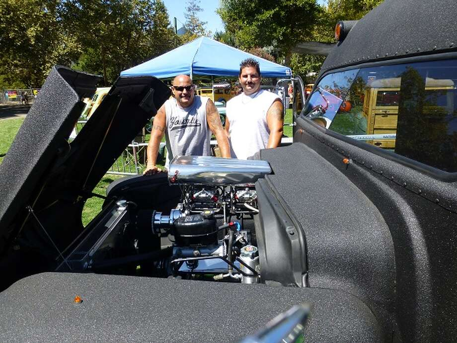 Darin McCullough and his friend and co-builder on the bus, Ryan Grishkin, standing behind the engine bay, with its 1,000-horsepower engine.
