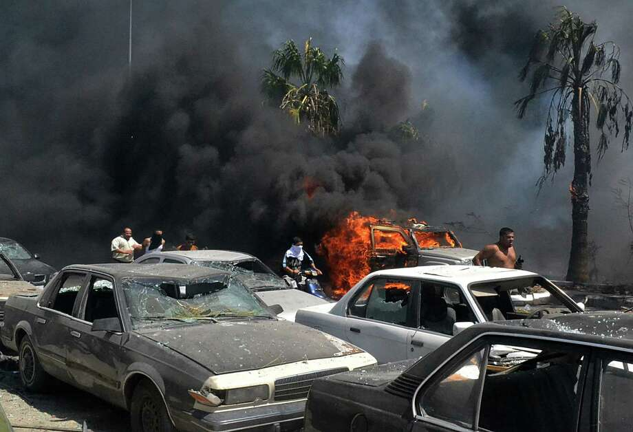 Men run between burning cars at the site of an explosion in Tripoli. The blast comes amid rising tensions in the country resulting from Syria's civil war. Photo: Associated Press