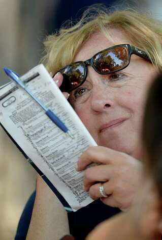 Carlene Spires of Andover, Mass. reads her racing program Friday afternoon, Aug 23, 2013, at Saratoga Race Course in Saratoga Springs, N.Y. The Travers Stakes runs Saturday. (Skip Dickstein/Times Union) Photo: SKIP DICKSTEIN