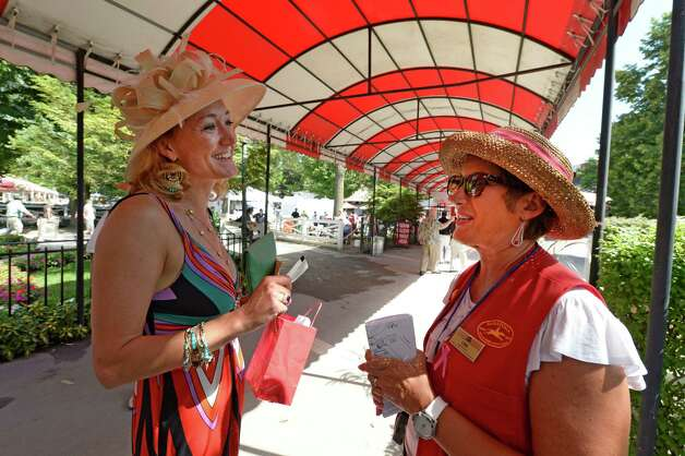 NYRA Customer service person Lisa Boland, right, assists patron Lisa Petrovic with a question Friday afternoon, Aug. 23, 2013, at Saratoga Race Course in Saratoga Springs, N.Y. (Skip Dickstein/Times Union) Photo: SKIP DICKSTEIN