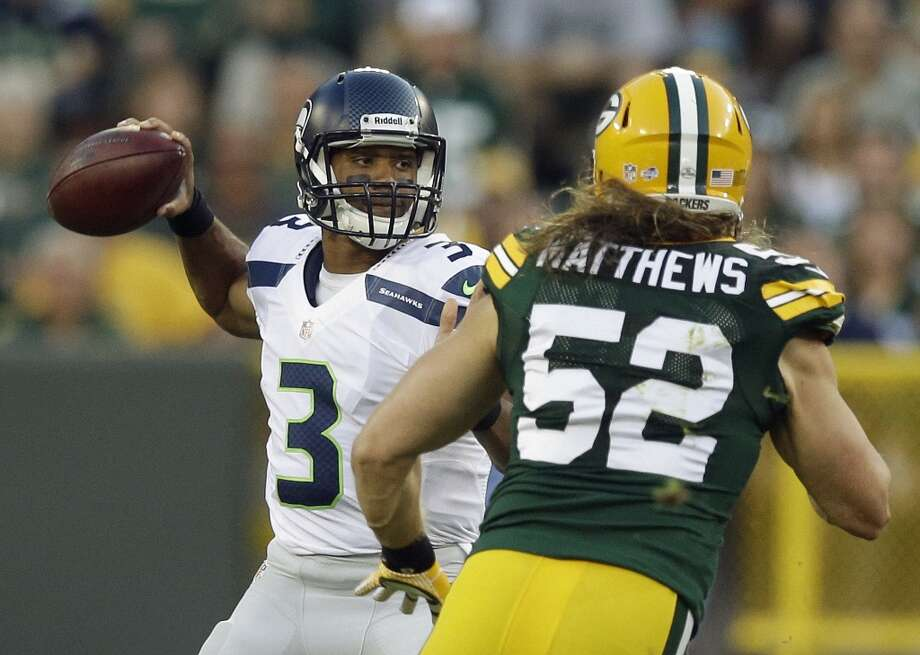 Seattle Seahawks quarterback Russell Wilson tries to avoid the rush of Green Bay Packers outside linebacker Clay Matthews (52) during the first half of an NFL preseason football game Friday, Aug. 23, 2013, in Green Bay, Wis. (AP Photo/Morry Gash) Photo: AP