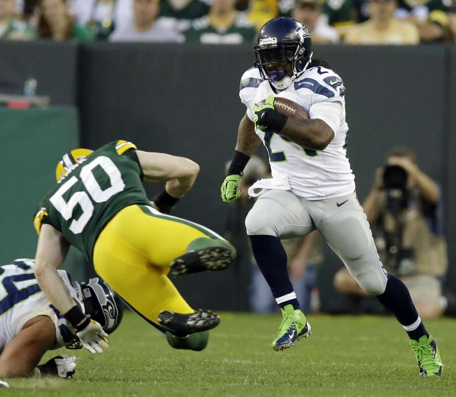 Seattle Seahawks' Marshawn Lynch runs past Green Bay Packers' A.J. Hawk (50) during the first half of an NFL preseason football game Friday, Aug. 23, 2013, in Green Bay, Wis. (AP Photo/Tom Lynn) Photo: ASSOCIATED PRESS