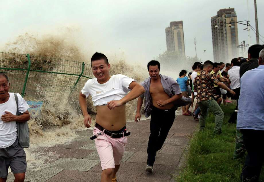 "This picture taken on August 22, 2013 shows onlookers running away from huge waves from the ""Haining tide"" - a daily occurrence when the river tides hit the banks of the city - as they surge higher than usual due to the influence of Typhoon Trami in the region in Haining, in eastern China's Zhejiang province. Typhoon Trami, the 12th typhoon to hit China this year, brought rainstorms and wreaked havoc in eastern China after landing in Fujian Province early on August 22.  The tides there have attracted spectators for the past two millennia, and it is the scene of an annual Tide-Watching Festival in late summer. Photo: STR, AFP/Getty Images / AFP"