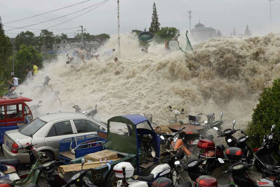 In this Thursday Aug. 22, 2013 photo, spectators flee as waves created by a tidal bore crash over a barrier on the Qiantang river at Haining, in east China's Zhejiang province. About 30 people were injured when they were caught too close to the river while viewing the annual tidal bore, which occurs when sea water from an unusually high tide funnels into the river, creating high waves. Photo: Associated Press / CHINATOPIX
