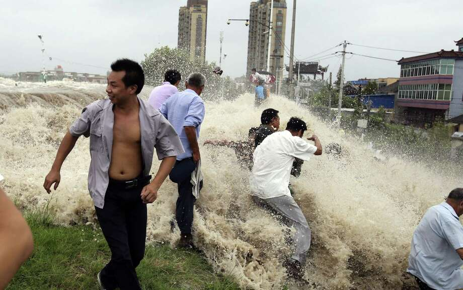"This picture taken on August 22, 2013 shows onlookers being washed away from huge waves from the ""Haining tide"" - a daily occurrence when the river tides hit the banks of the city - as the waves surged higher than usual due to the influence of Typhoon Trami in the region in Haining, in eastern China's Zhejiang province. Photo: STR, AFP/Getty Images / AFP"