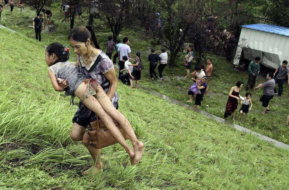 "This picture taken on August 22, 2013 shows a woman carrying an injuried girl after they were washed down a hill from huge waves from the ""Haining tide"" - a daily occurrence when the river tides hit the banks of the city - after a wave surged higher than usual due to the influence of Typhoon Trami in the region in Haining, in eastern China's Zhejiang province. Photo: STR, AFP/Getty Images / AFP"