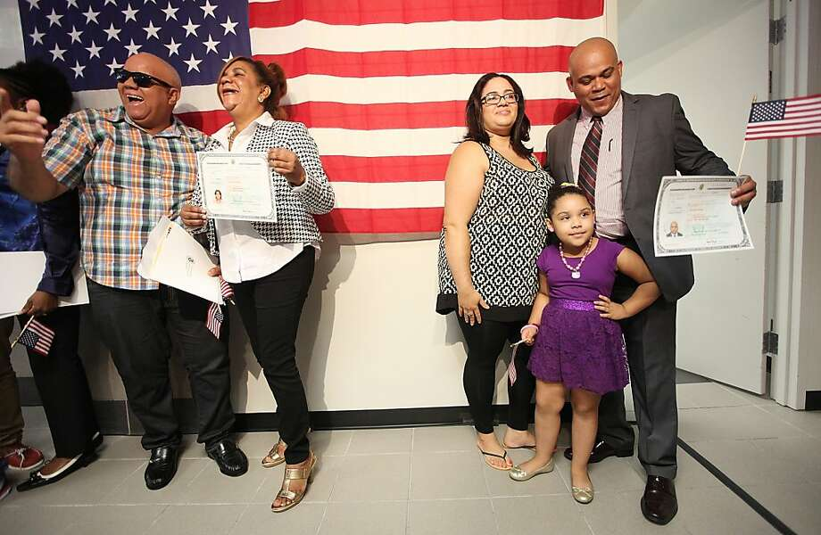New citizen Alfonso Vasquez (R) poses for photos with Welkenia Batista and Arialla Castillo, 4, in front of an American flag after a naturalization ceremony for approximately 150 citizenship candidates at Federal Plaza in Manhattan on August 23, 2013 in New York City. Homeland Security Secretary Janet Napolitano administered the Oath of Allegiance at the ceremony and is resigning from the Homeland Security position to become the next University of California president.  Photo: Mario Tama, Getty Images