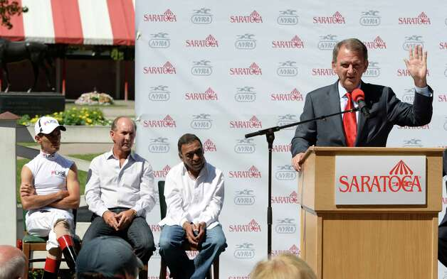 NYRA president Chris Kay, right, speaks before unveiling a plaque which named the top three jockeys in the history of the Saratoga Race Course Friday afternoon, Aug. 23, 2013, at Saratoga Race Course in Saratoga Springs, N.Y.  The three top jockeys seated to the left are John Velazquez, left Jerry Bailey and Angel Cordero Jr.  (Skip Dickstein/Times Union) Photo: SKIP DICKSTEIN