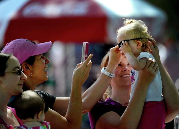 Sylvia DeCarr of Guilderland, left, takes photos of Meghan Vess with the help of her mom Melanie Vess of Clifton Park, right, Friday afternoon, Aug. 23, 2013, at Saratoga Race Course in Saratoga Springs, N.Y. (Skip Dickstein/Times Union) Photo: SKIP DICKSTEIN
