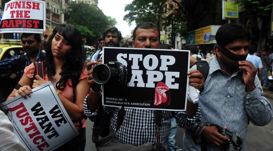 Photographers hold signs Friday during a protest march against the gang-rape of a fellow colleague in Mumbai. Five men attacked the female photographer in India's financial hub. Photo: Indranil Mukherjee / Getty Images
